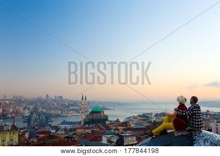 Bird Flight View of Middle East Megapolis and romantic Couple sitting on roof of high Building at Morning