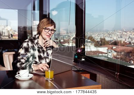 Cute female Freelancer working on Computer at Roof Top Cafe sitting at wood Table next to Window with City View