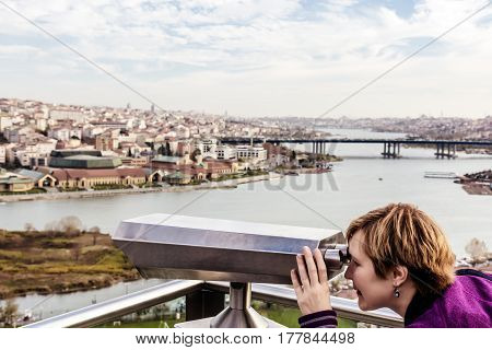 Female Tourist in casual clothing overlooking City Panorama throw Binoculars at popular touristic Spot