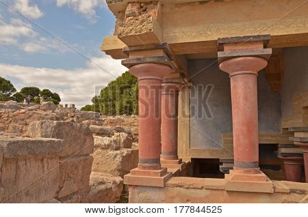 Ruins of the Knossos palace with red columns. Trees and the sky with clouds in the background