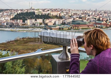 Person looking throw tourists Binoculars at City and River View at popular Travel Spot