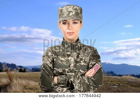 Female soldier in camouflage on landscape background