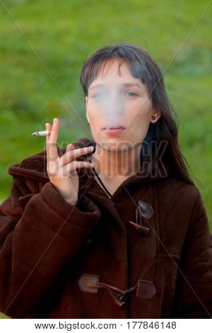 Pretty woman with long hair smoking in the park