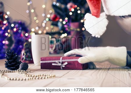Person in Santa Hat and Gloves preparing gift in decorated box putting it on wooden floor next to illuminated christmas tree