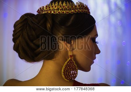 Eastern girl brunette in a red dress with beautiful hairstyle earrings of beads and a crown on her head and bright makeup. Female style. Mysterious eastern woman. Blue light. Eastern model