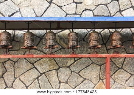 Prayer wheels with stone wall background in buddhism temple in countryside of Nepal