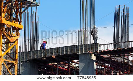 Engineer And Workers On High Building Construction Site.