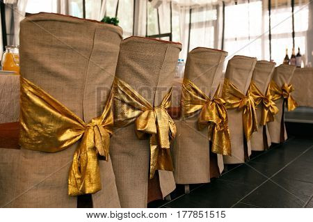 Wedding chair decoration. Beige covers and gold bows on the backs of chairs. Horizontal photo