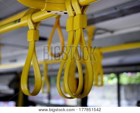 yellow plastic armrests passengers on a city bus