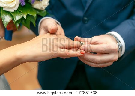 The groom puts on an engagement ring on the finger of the bride. Close-up horizontal photo