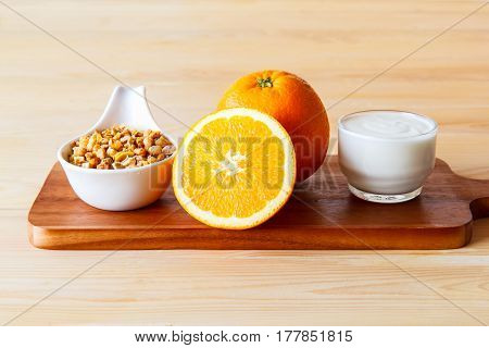 focus the dried cereal with yogurt Parfait and orange for healthy put on the wood background Healthy eating concept.