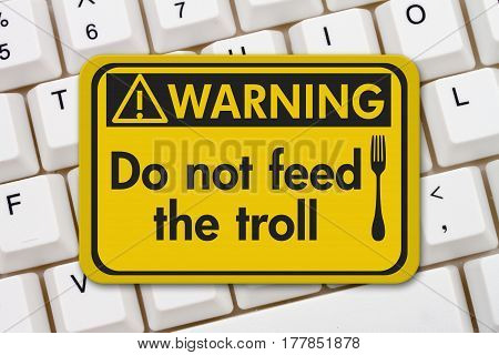 Feeding the troll warning sign A yellow warning sign with text Do not feed the troll and fork icon on a keyboard 3D Illustration