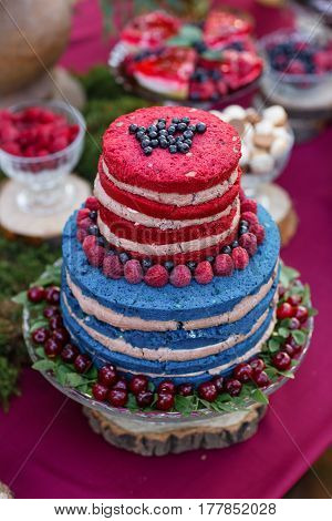 Wedding cake with berries, Blueberries and raspberriess on the table. Fourchette, a lot of food on the table