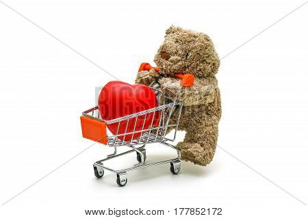 Isolated Teddy Bear Toy Is Pushing The Trolley Cart  With Red Sponge Heart In It On White Background