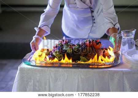 ham cooking on grill with flames. Dish served with fire chef on background.