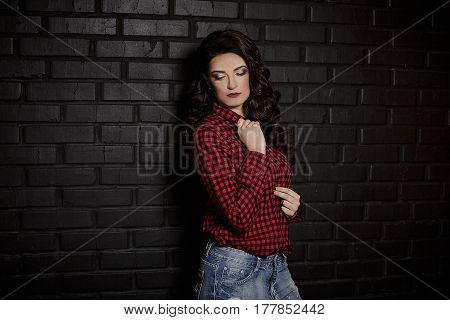 Fashion pretty young woman blowing red lips making air kiss looking down closed eyes red checkered shirt over black background. Fashion hairstyle and makeup.