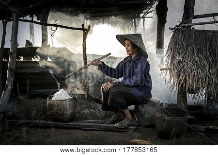 Woman working on salt field in Thailand Boiling rock salt crystallized salt from boiled saltwater to dried up the basket travel landmark in Thailand
