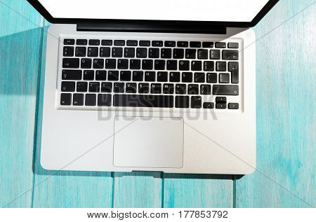 Modern laptop computer on blue table, view from above