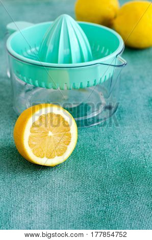 Fresh lemons with citrus squeezer on turquoise background. Copy space, vertical