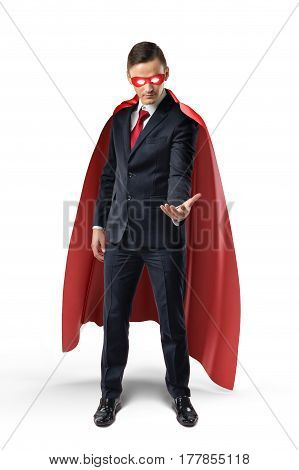 Businessman in a red cape and red eye mask looking at his hand and holding something on white background. Business and success. Corporate hero. Superpowers and coaching.