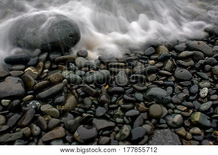 Smooth Beach Stones With Wave At Ocean