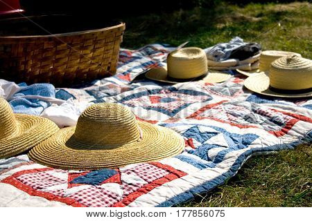 Old fashioned picnic scene with quilt and hats.