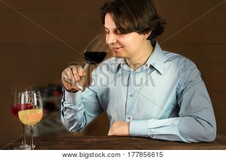 A photo of an enologist tasting wine at a winery, smiling, with more glasses in front of him