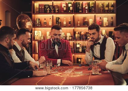 Group of men playing poker in gentlemen's club