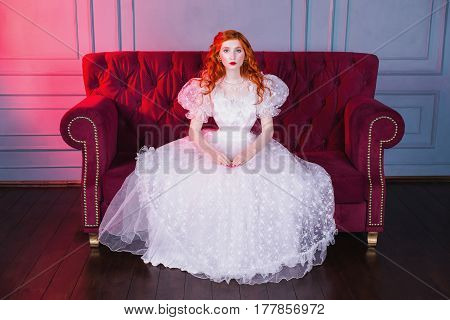 Woman princess with long red curly hair in a white vintage wedding dress with white pearl earrings on her ears. Red-haired princess with pale skin blue eyes a bright unusual appearance sitting on a red couch. Redhead princess