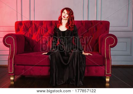 Beautiful girl with red hair and natural make-up and pale skin. A woman in a black retro dress sitting on a red couch. Model posing in studio. The unusual appearance. Insidious wicked witch woman.