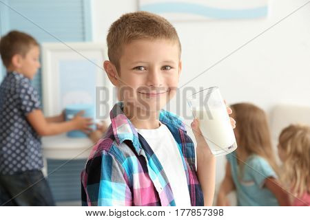 Cheerful little boy holding glass of milk and standing in the room