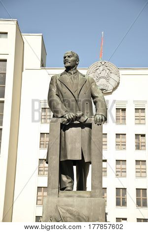 MINSK BELARUS - March 23 2017. A statue of the leader of the USSR Comrade Lenin against the background of the Belarusian coat of arms that hangs on the building of the parliament of the Republic of Belarus