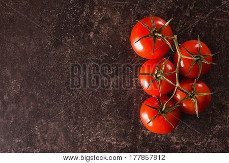 Red tomatoes lie on a dark marble table. Space for text and design. Flat lay copyspace. Ingredients for salad. Ingredients for a healthy diet