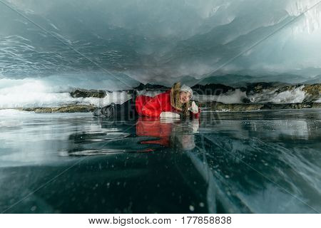 Woman is a tourist and a traveler in the ice. The girl crawls creeps in a small gorge of ice. From above, a sheer dangerous ice layer sinks. From the bottom is a very deep and clean lake with cracks. Location of the lake is Lake Baikal.