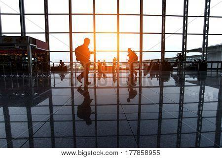 Travelers walk through an airport terminal,Passengers walking through a modern airport terminal