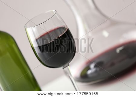 Wineglass with red wine and decanter on light background