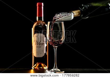 Pouring red wine into decanter on dark background