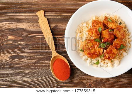Plate with tasty chicken tikka masala, rice and spice in spoon on wooden table