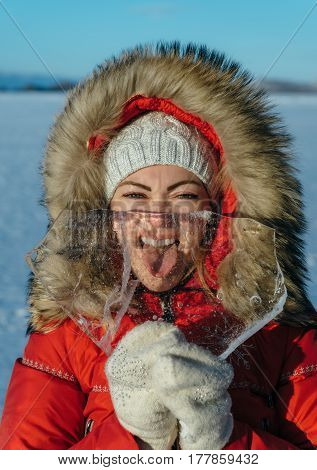 Funny girl with an icicle. A woman is a tourist and a traveler in the ice of Lake Baikal. Girl plays with a pure transparent ice show funny faces through it. Location of the lake is Lake Baikal, Siberia, Russia.