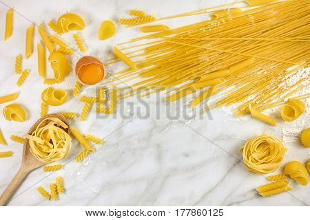 Various types of pasta on a white marble table with flour and an egg, forming a frame for text