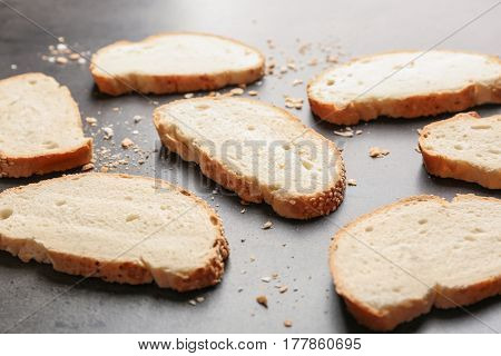Slices and crumbs of wheaten bread with sesame seeds on grey background