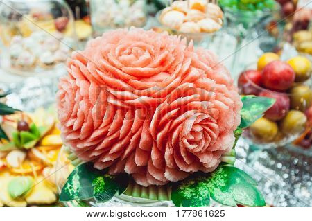 beautiful watermelon carving on the table on wedding candybar. a lot of desserts