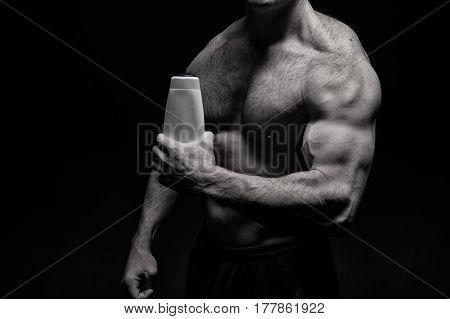 Handsome Bodybuilder Man With Muscular Body Holds Shampoo Bottle
