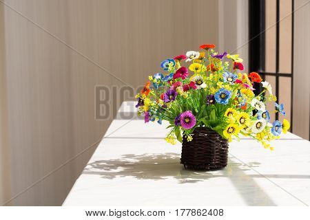 Colorful Flowers in Brown Wood Basket on White Table Beside Glass Window in morning with dramatic light shadow as Romantic Love Concept.