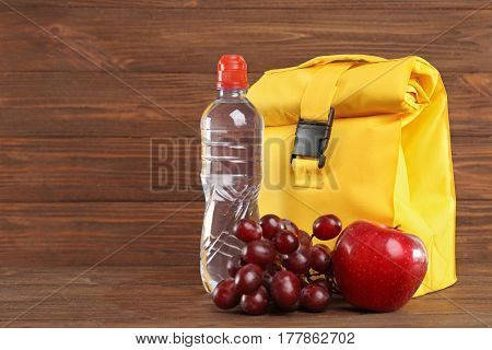 Yellow lunch bag, fruits and bottle of water on wooden background