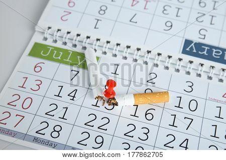 Broken cigarette pinned to calendar, closeup
