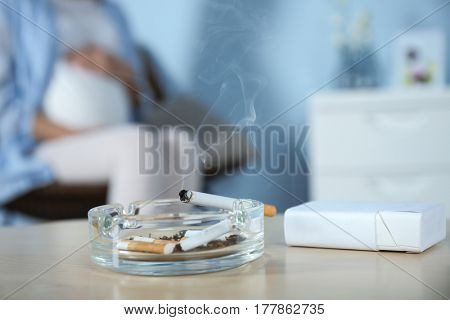 Cigarettes in ash tray and blurred pregnant woman on background