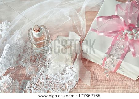 Beautiful gift boxes, perfume and bridal veil on light background