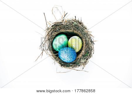 Three spotty-painted easter eggs in birds nest. Isolated over white background