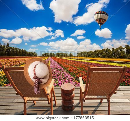 Concept of ecological tourism. Rural rest. Wooden chaise lounges  in the meadow with flowers.  Huge balloon flies over the field
